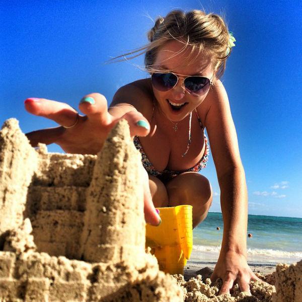 Дарья принимает участие и в развлечениях сына - строит с ним замки на песке