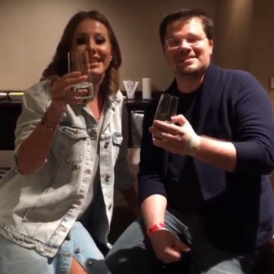Ксения и Гарик в гримерке. Поздравляют всех с Новым годом на ломаном английском. В стаканах вода!