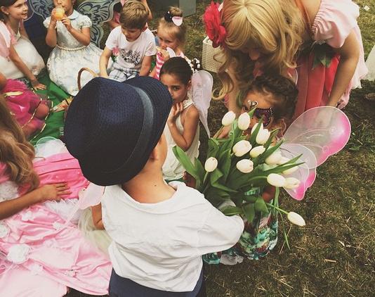 Сын Водонаевой с букетом белых тюльпанов на детском празднике