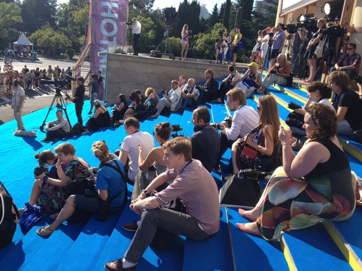 Журналисты сидят на парадной лестнице в ожидании следующей звезды