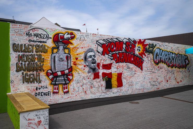Граффити с пожеланиями благополучия для Кристиана Эриксена в центре Копенгагена.  В центре стены портрет футболиста и подпись: