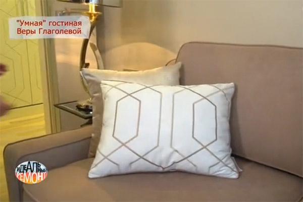 Диван российского производства в английском стиле. Он декорирован подушками, цвет которых сочетается с цветом рисунка на портьерах