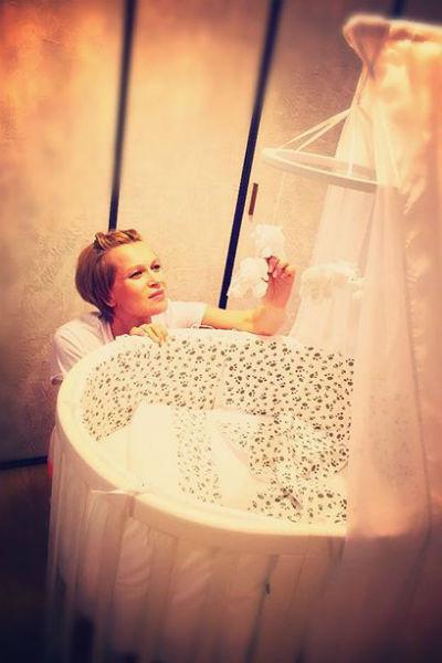Олеся Судзиловская у кроватки новорожденного