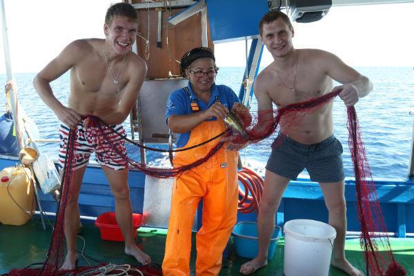 Русские ребята помогают рыбаку распутывать сети с уловом