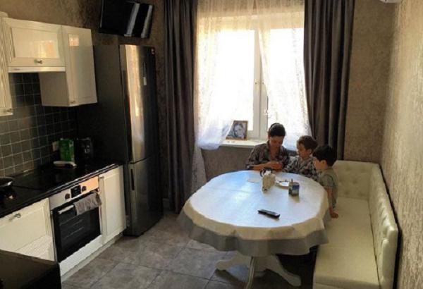 Юлия с сыновьями на фоне кухни